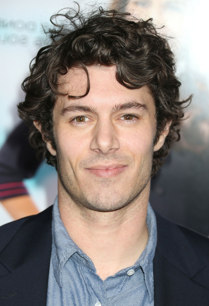 close up of adam brody, with messy short curly hair, brown eyes and bushy eyebrows, wearing denim shirt, and dark blue formal blazer