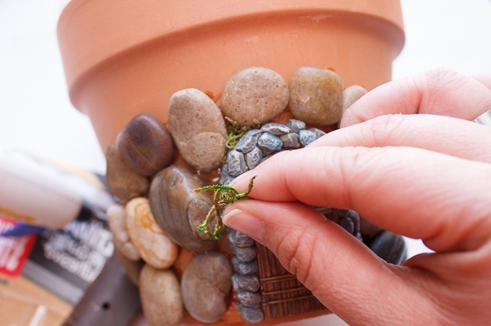 sticking green moss between pebbles, stuck on an orange ceramic pot, fairy garden ideas, tiny 3D door sticker, made of plaster or clay