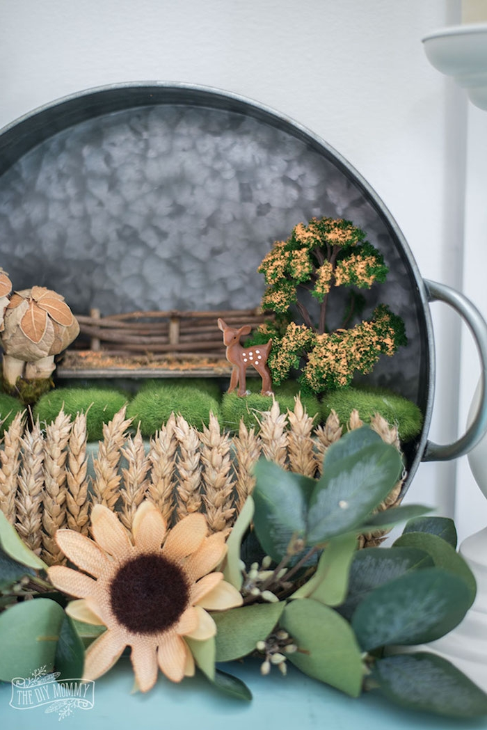 looking at the nearly completed fairy garden wreath up close, moss and tree figurine, tiny deer ornament, faux flowers and leaves