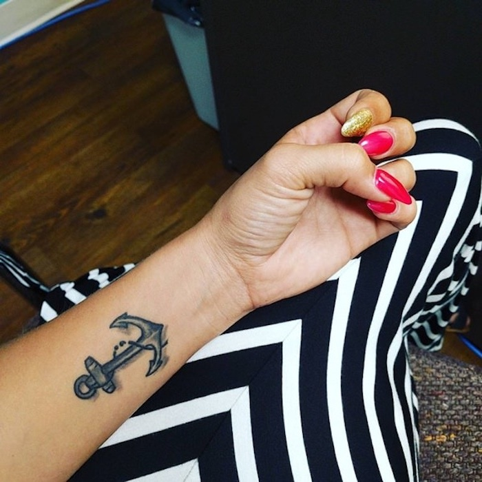 hot pink and gold, long sharp nails, worn by tan woman, with a dark gray anchor tattoo, featuring a chain with a small semicolon, semicolon tattoo meaning, long striped black and white skirt