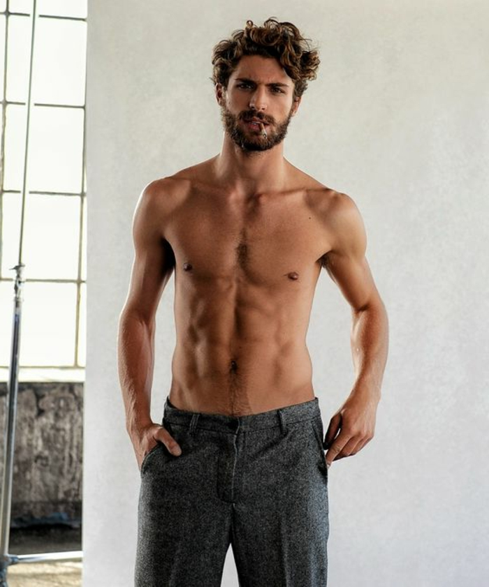 lean and muscular topless man, with a beard and mustache, smoking a cigarette, haircuts for men with curly hair, dark gray tweed trousers