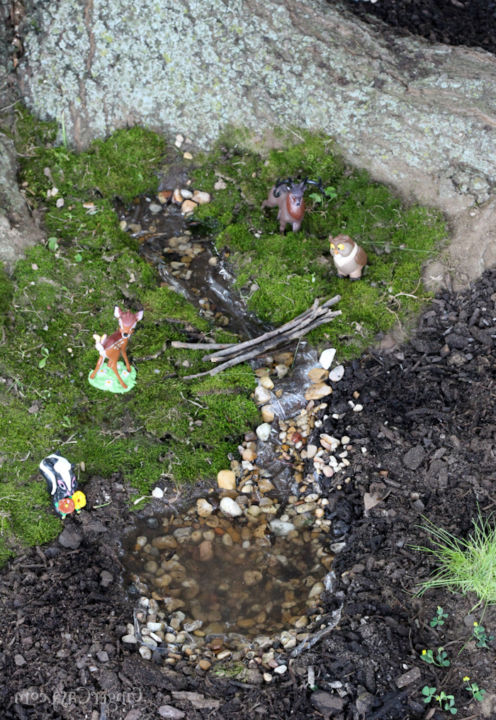 plastic animal figurines, Bambi and his friends, placed on green moss, near artificially made miniature stream, with pebbles and a tiny bridge, made of sticks, fairy garden images