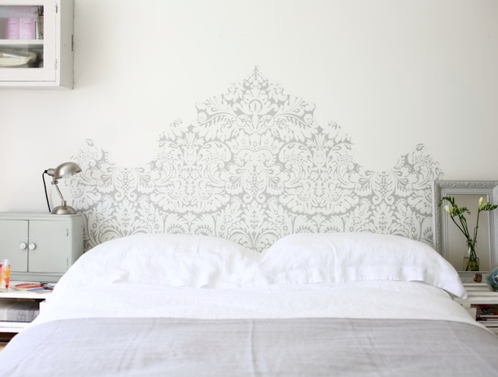 headboard-like decoration, in baroque style, painted in pale gray behind a double bed, wall art décor, small vase with white flowers, silver bedside lamp