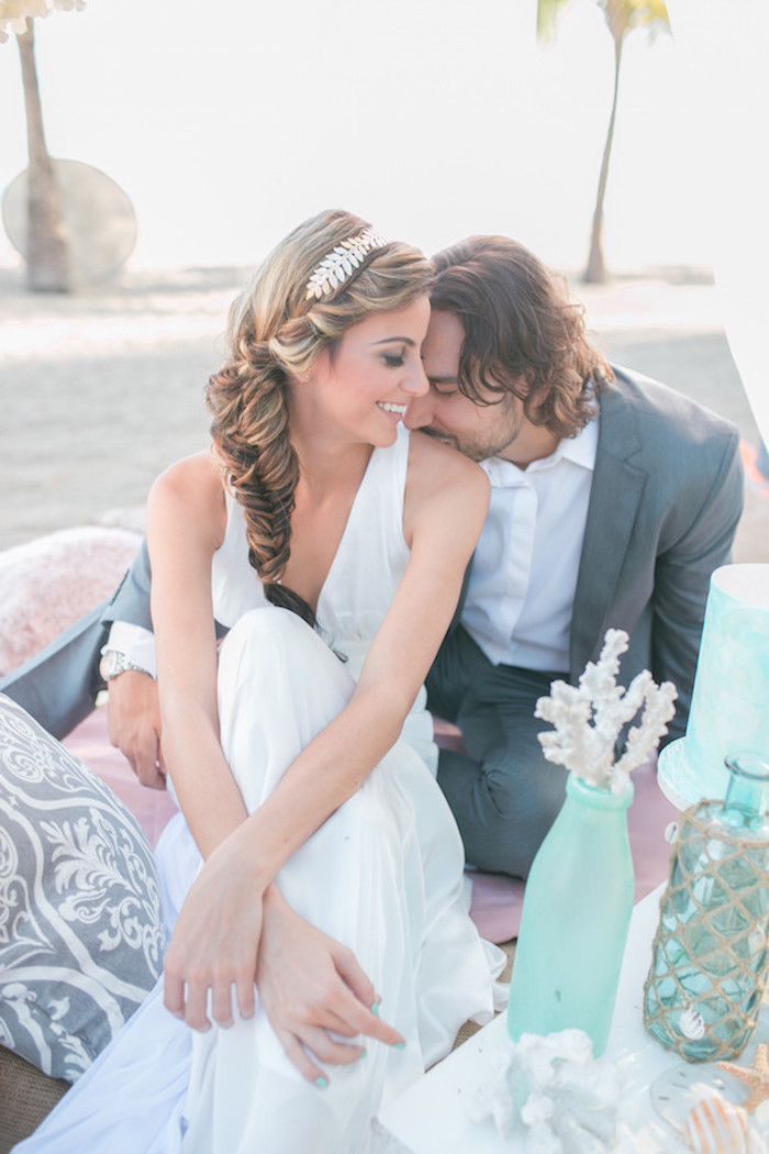 intimate image of a groom, wearing grey suit and white shirt, sitting next to a bride, in a long white gown, and kissing her shoulder, wedding dresses for beach wedding, marine-inspired decorations and cushions