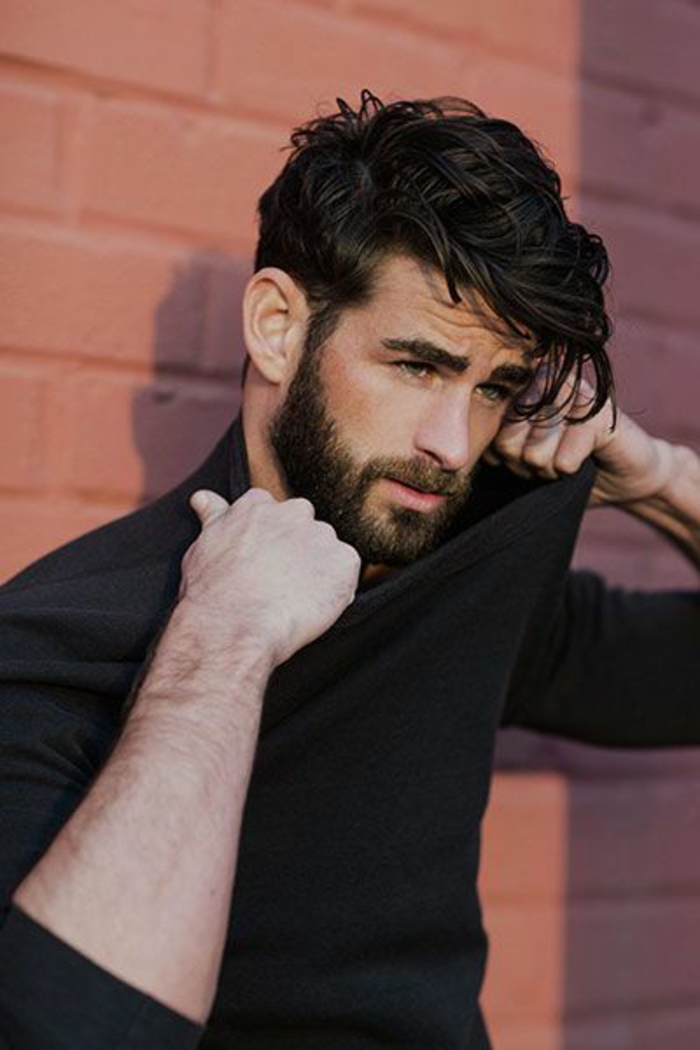 man pulling his black jumper with both hands, with black shiny hair, wavy and layered, haircuts for curly hair, beard and mustache, thick bushy eyebrows