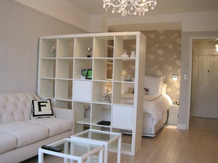 studio apartment design, white cupboard with many, square storage compartments, half-separating sleeping area, from living room area, white sofa and two square coffee tables