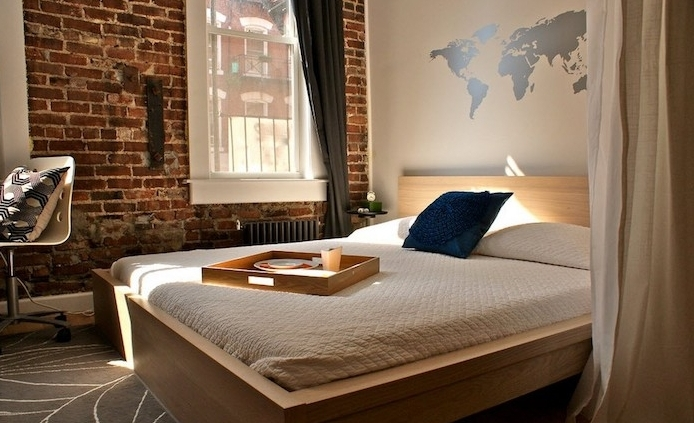brick wall inside a sunlit room, other visible wall is white, with a silver world map wall art décor, simple bed with wooden food tray