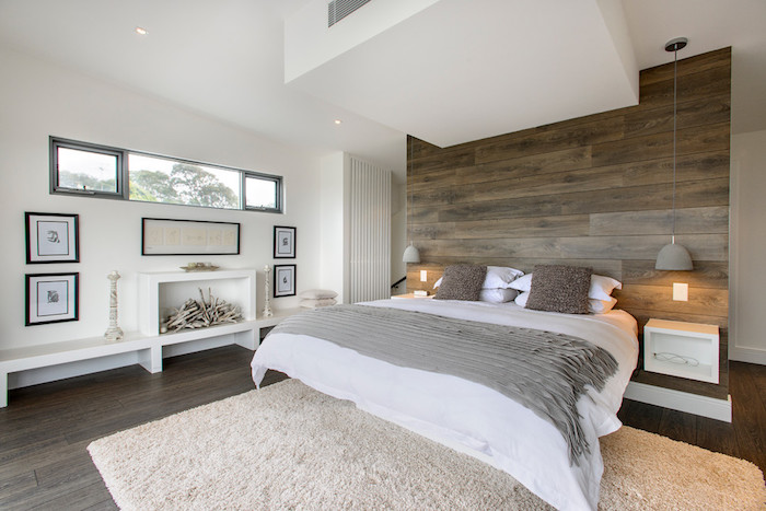 several framed images, and a white decorative fireplace, beneath a long narrow window, wall decor ideas, wooden planks covering one wall, near a double bed
