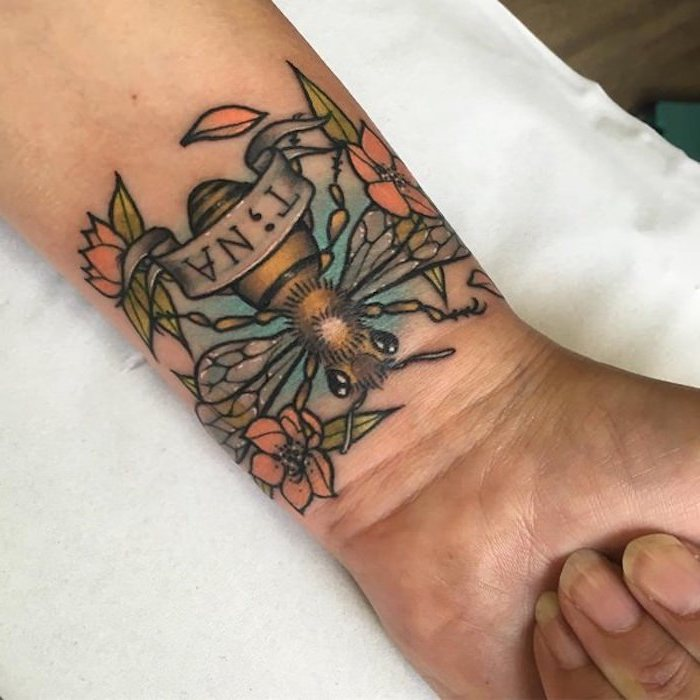 wrist tattoo featuring a large bee, several orange flowers, with green leaves and thick black outlines, and a banner with the name tina written in black, the i substituted for a semicolon tattoo