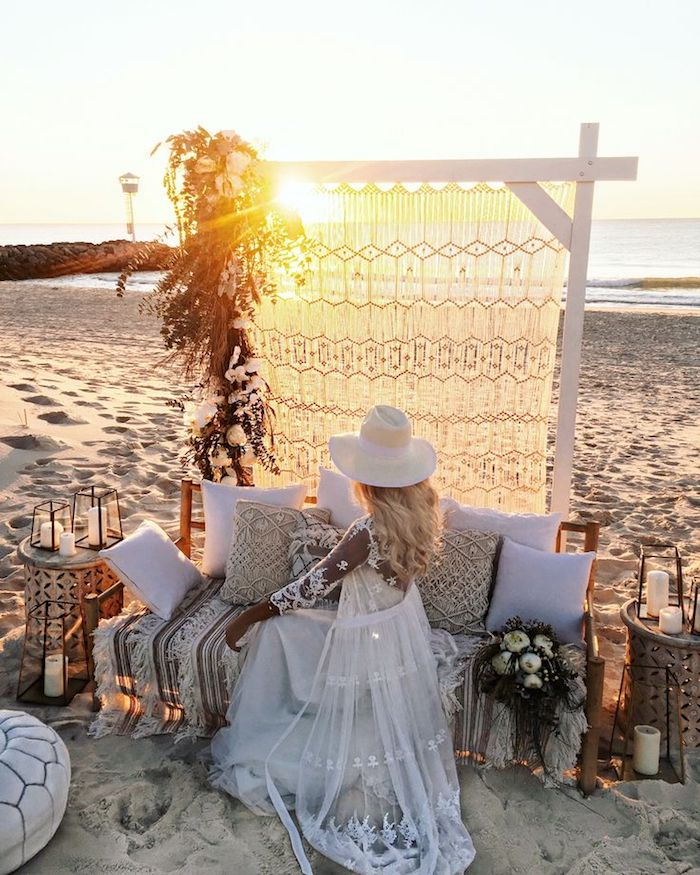 beach weddings in florida, boho decor on a sandy shore, bride in long dress and hat, and sheer white embroidered maxi cardigan, sitting on a bench covered in cushions, and watching the sunset
