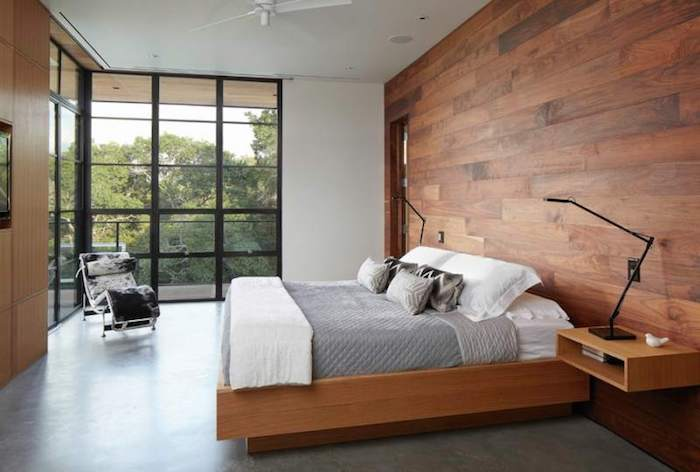 wooden planks in warm brown color, covering one wall of a bright room, master bedroom ideas, large corner window, smooth gray floor