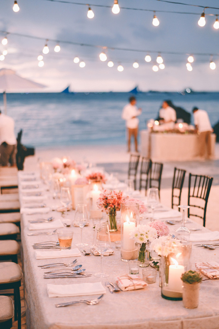 long set table, with cutlery and plates, glasses and candles, small flower bouquets in white and pink, on a beach near the sea, florida destination weddings, two rows of string lights