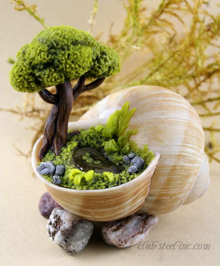 snail shell in pale beige, placed on several pebbles, and filled with a tiny garden, made from colored moulding clay, fairy garden images, tree and glass, lake and stones