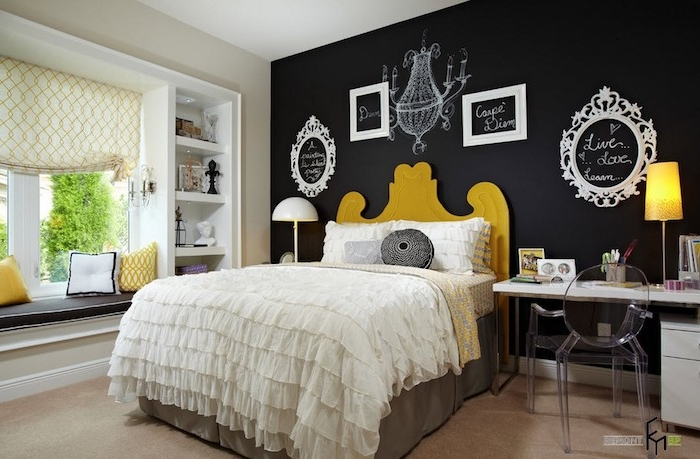 chandelier drawing white, on black wall, decorated with four empty frames, containing messages written in white chalk, large wall art, bed with frilly covers ,and bright yellow headboard
