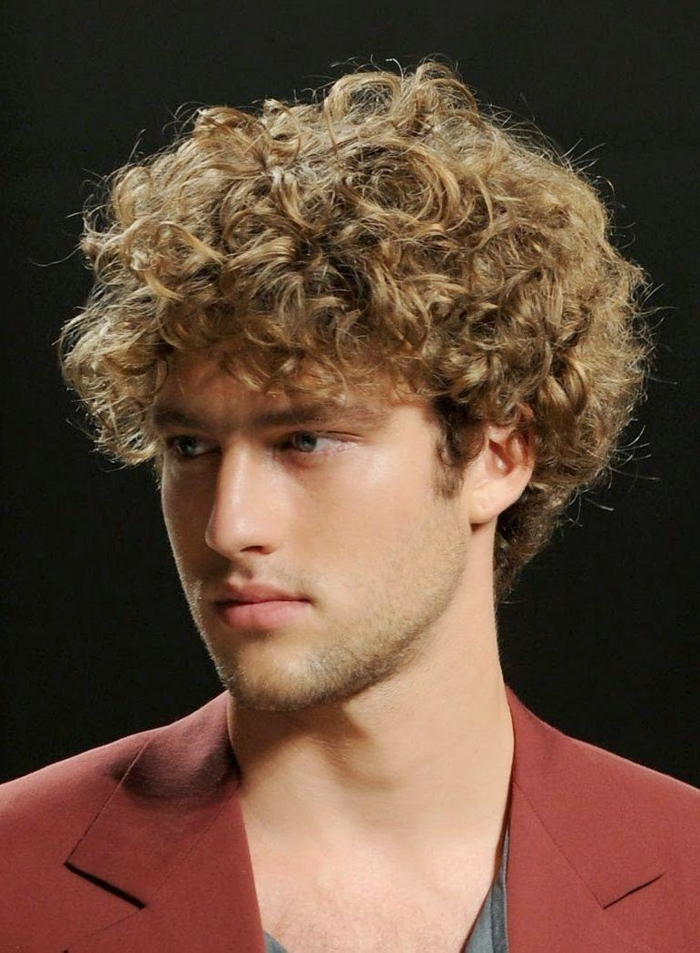red blazer and grey top, worn by blue-eyed man, with voluminous blonde curly hair, guys with curly hair, stubble on chin and lip, and a black background