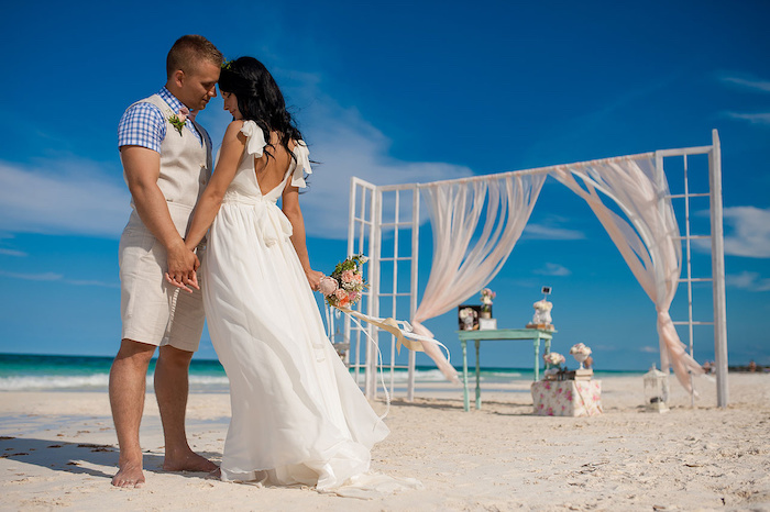 chequered shirt in white and blue, combined with off-white vest and shorts, worn by groom, holding hands with bride in white gown, on beach with fine sand