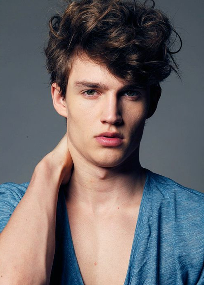 bouncy messy brunette curls, worn by slim young man, hairstyles for curly hair, pale blue t-shirt, with deep v-shaped neckline