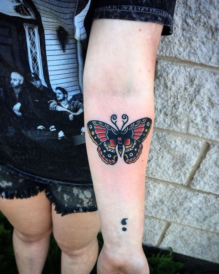 dark butterfly tattoo, with bold outlines, decorated with red, yellow and white, near a black semicolon tattoo, what does a semicolon tattoo mean, arm and wrist tattoos