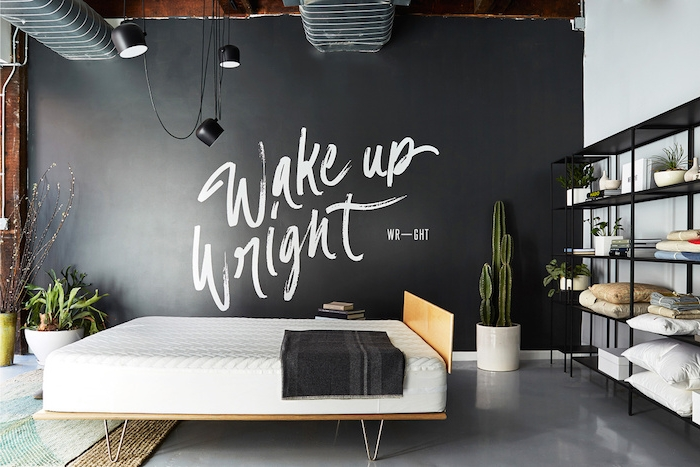 black wall with large bold white writing, inside industrial-style room, smooth pale gray floor, hanging lights and pipes on the ceiling, master bedroom ideas, black metal shelves