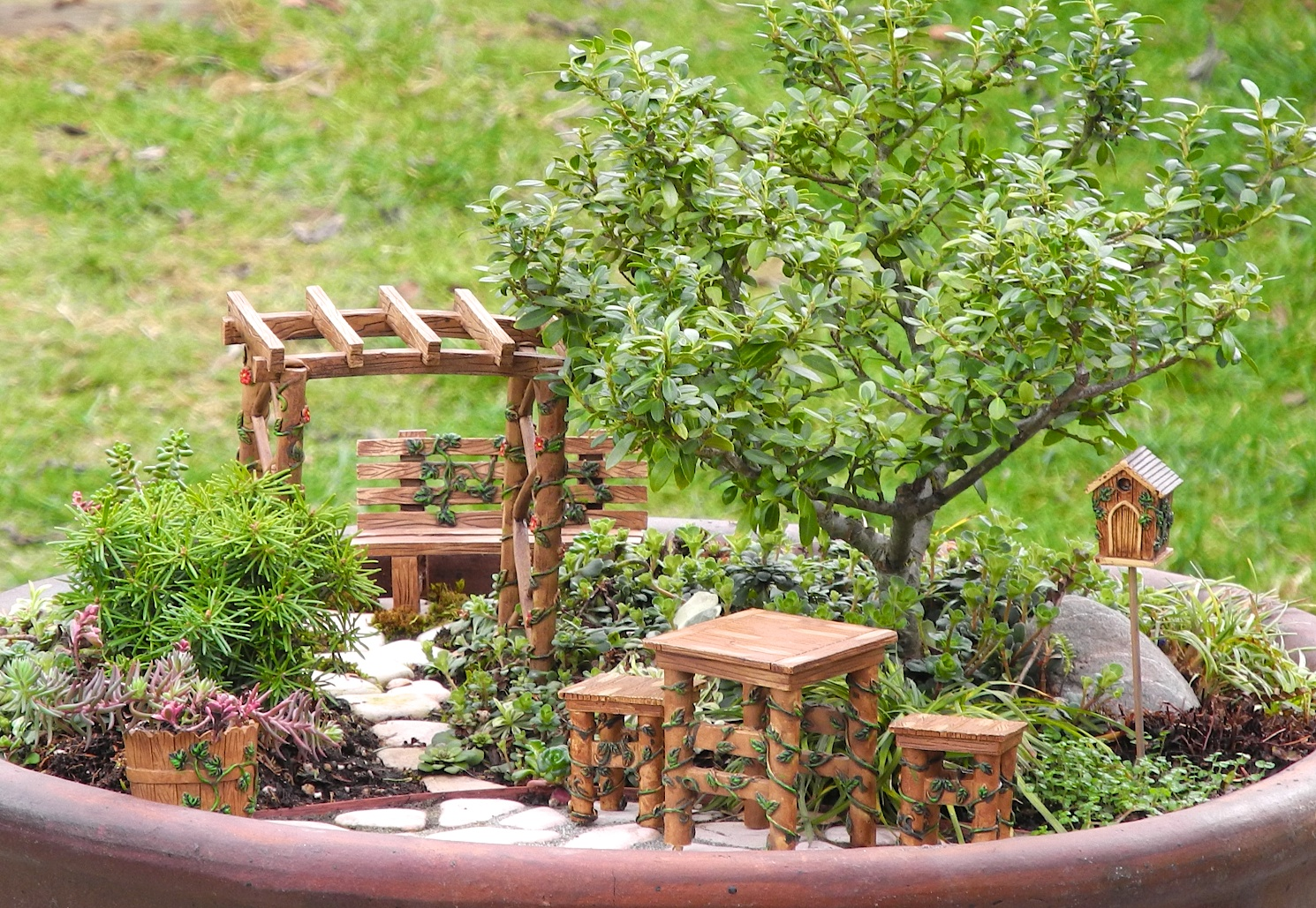 gazebo and bench, table and two stools, bucket and bird house, all made from wood-like material, in a large pot, containing pebbles and plants, and a green bonsai tree