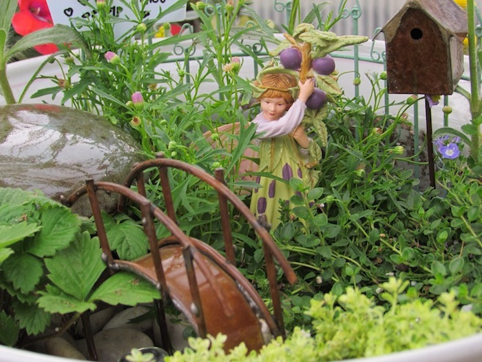 brown metal bridge figurine, placed inside a small garden, near fairy statuette, in white and green dress, and holding a branch with purple berries, fairy garden images, miniature birdhouse and stones