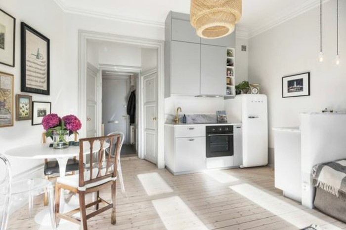 round small dining table, with four mismatched chairs, inside a bright room, with pale wooden floors, kitchenette and several framed images, small apartment ideas
