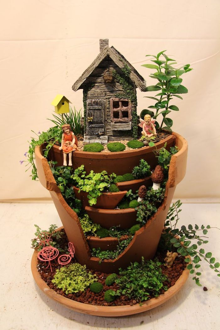 layered-effect broken ceramic pot, decorated with a tiny house, miniature birdhouse and two fairy figurines, fairy garden images, several different small green plants