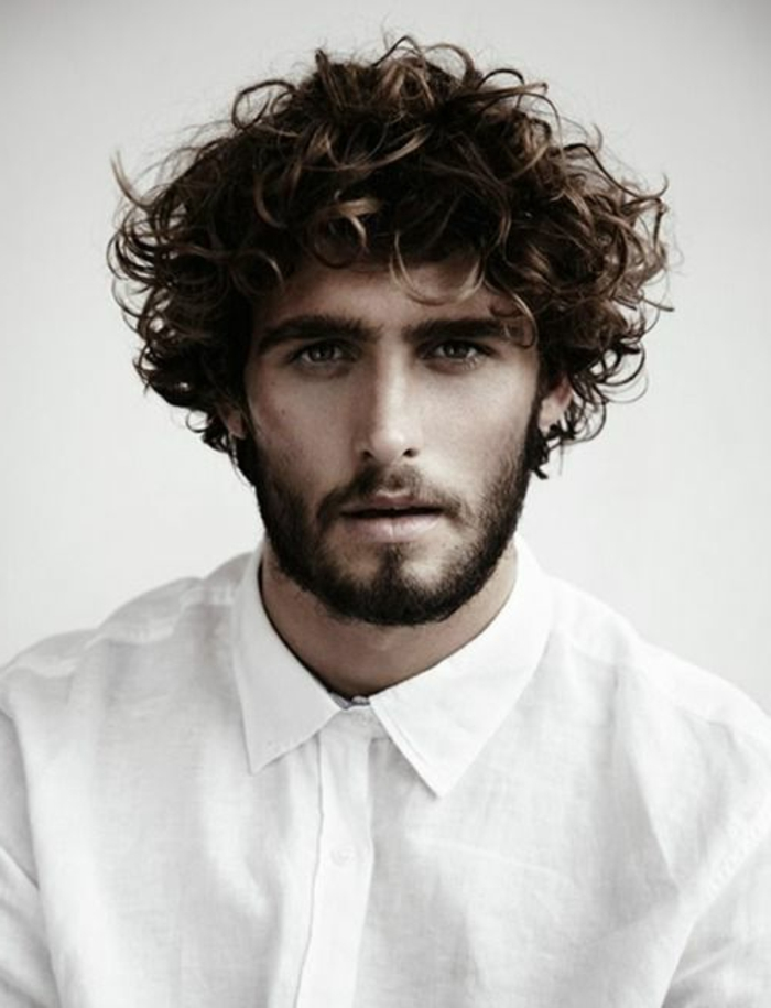 bushy eyebrows and a beard with mustache, worn by man in white linen shirt, unruly voluminous hair, guys with curly hair
