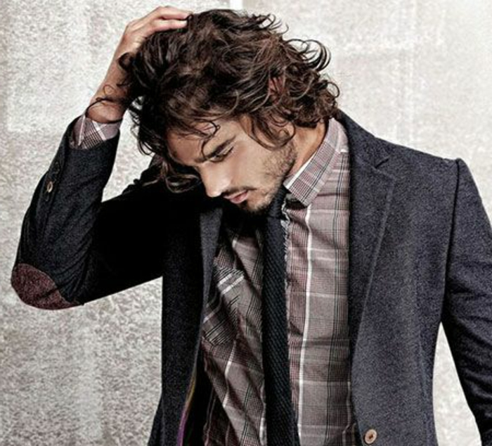 guys with curly hair, brunette man with tousled hair, wearing dark grey blazer, with elbow patches, over brown plaid shirt, stubble and mustache