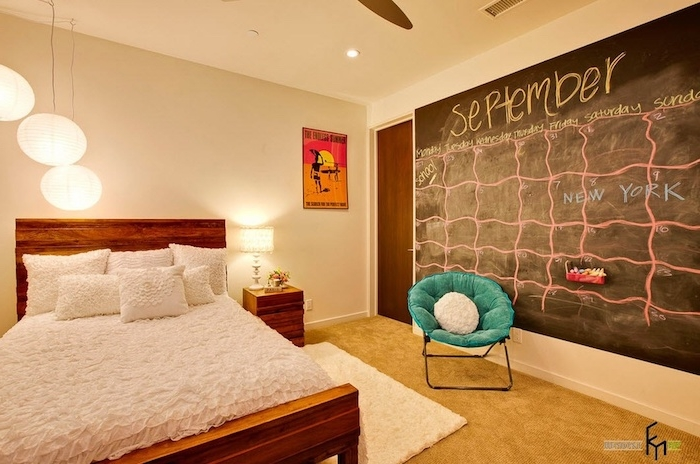 blackboard with calendar for september, drawn in yellow and pink chalk, on bedroom wall, near teal chair and wooden bed