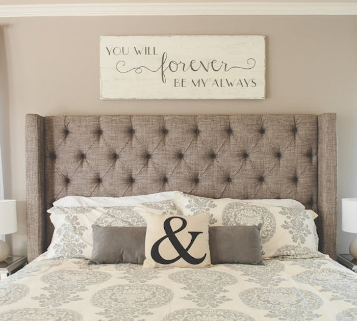 romantic message spelled in gray, on a cream-colored wooden board, hanging over a double bed, with beige soft headboard, and cream and gray bedding