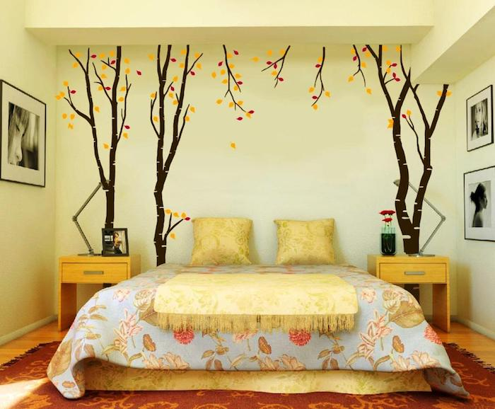 autumn trees with yellow and red leaves, painted on a pale yellow wall, creative wall decor ideas, near a double bed with floral covers, yellow tasseled throw, and two matching cushions