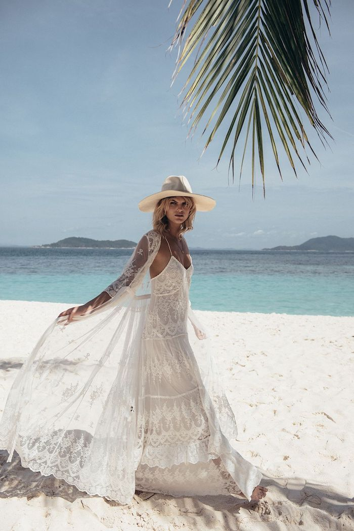 sheer oversized lace cardigan, worn over an embroidered lace maxi dress, casual beach wedding dresses, by blonde model, with yellow sun hat, walking on a sandy white beach