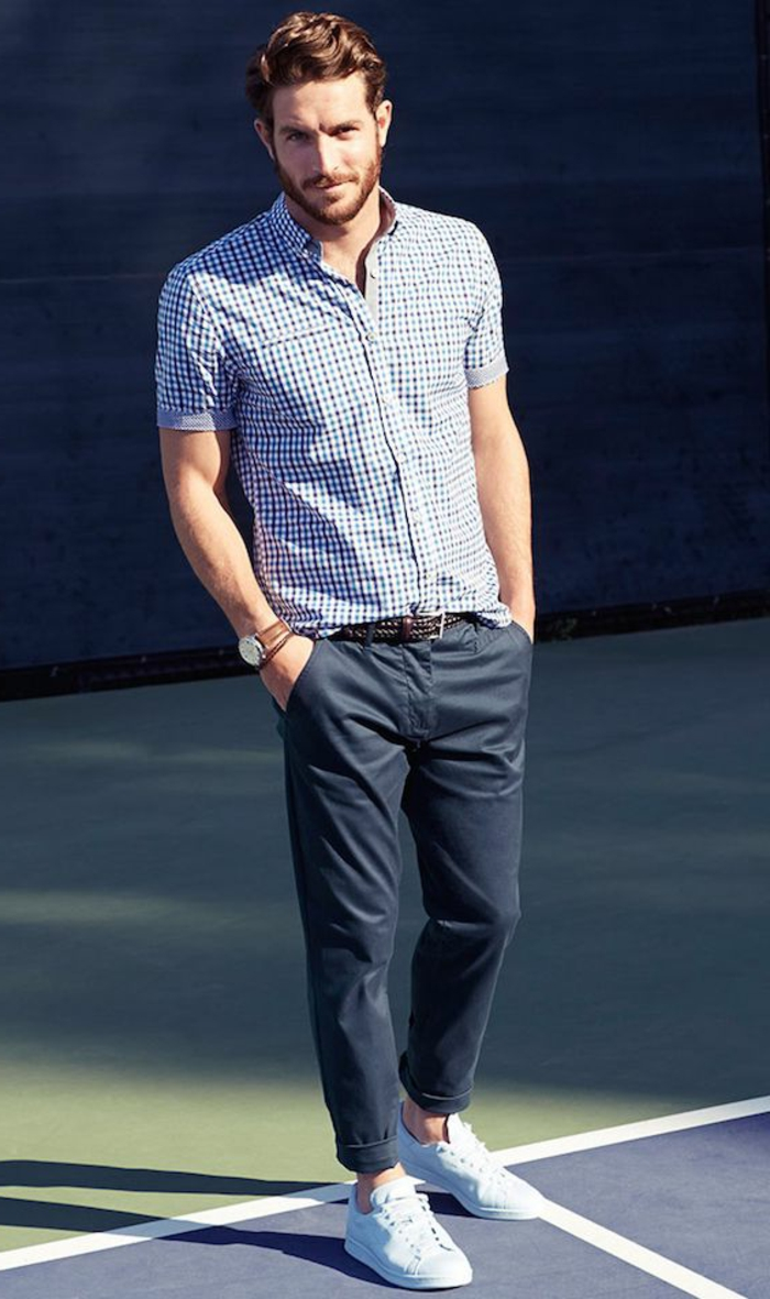full size photo of a man, with blue chequered short-sleeved shirt, and dark blue trousers, with his hands in his pockets, chestnut wavy brown hair, haircuts for curly hair