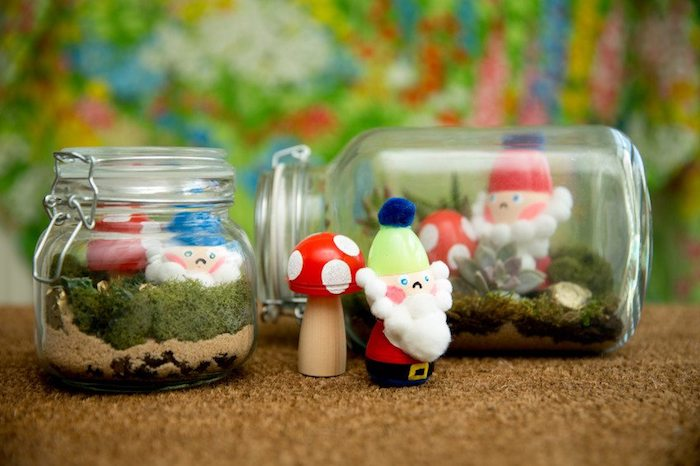 jars with snap lids, filled with fine beige sand, green moss and succulent, with little figurines, succulent fairy garden, painted wooden mushrooms and gnomes