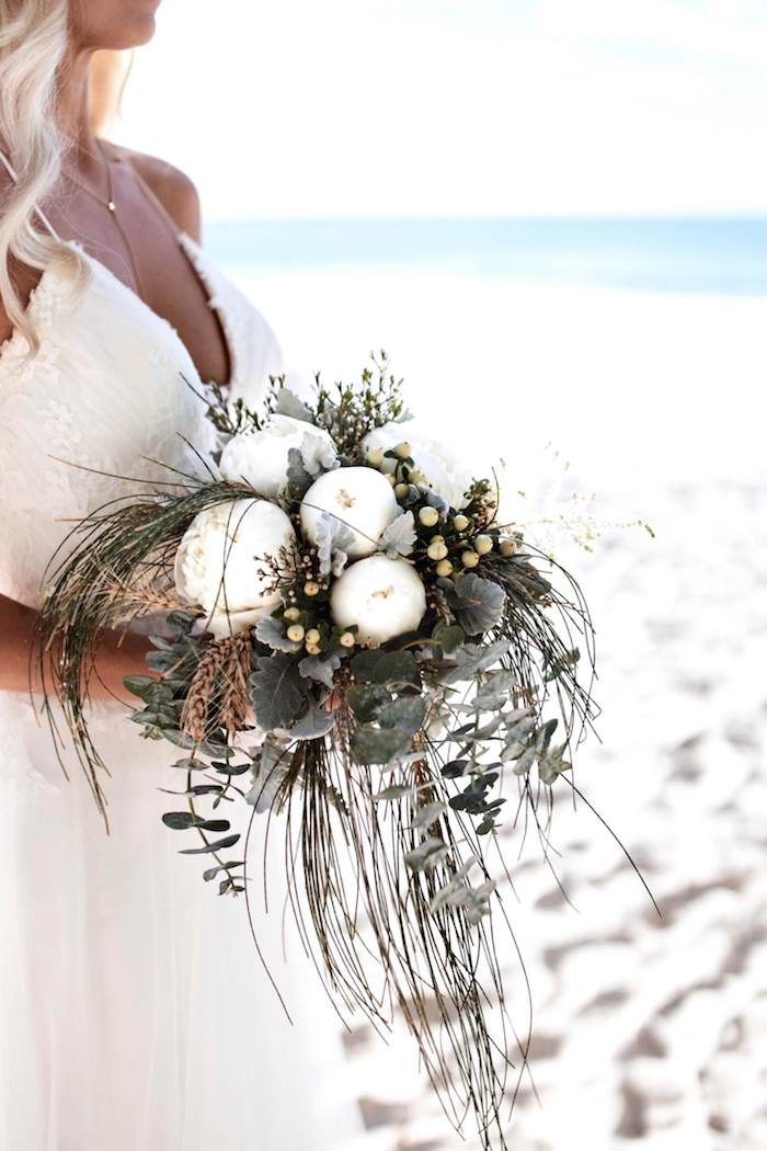 bouquet with white peonies, and various green plants, held by tanned blonde bride, wearing long white gown, and standing on a sandy shore near the sea, beach weddings in florida, white fine sand