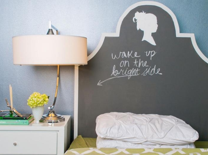 message written in chalk, on black headboard, with silhouette drawing of a female head, near small bed with light green covers, cool decor ideas