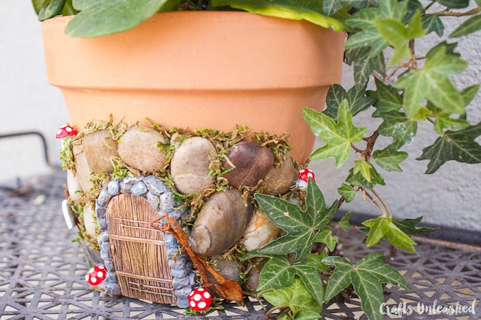 orange ceramic pot, decorated with pebbles, moss and a small door, made from painted moulding clay, ivy and other plants inside, fairy garden ideas