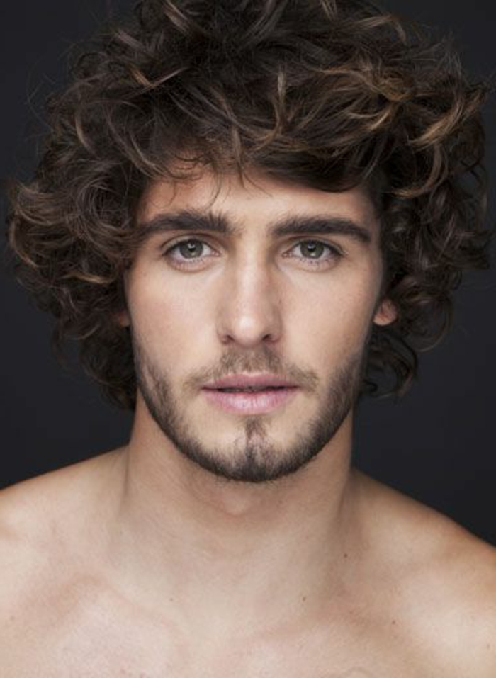 haircuts for men with curly hair, topless man with short beard and a mustache, brown eyes and bushy eyebrows, voluminous unruly brunette hair