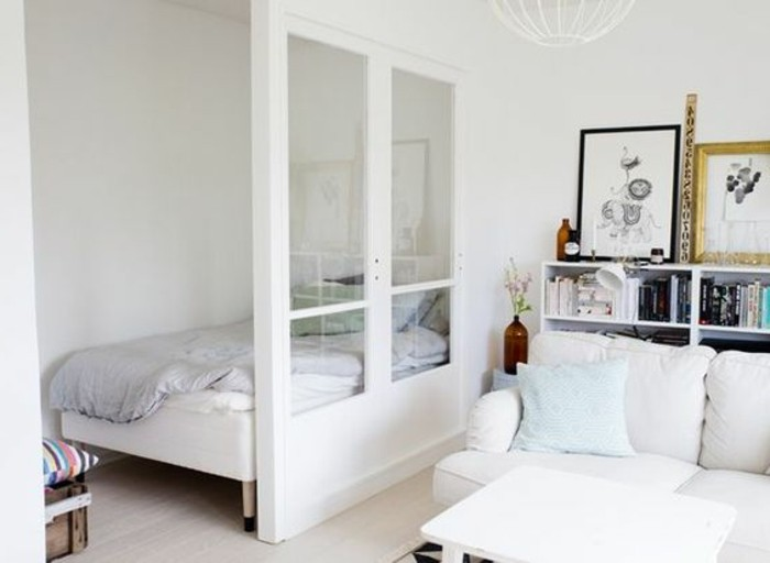 sleeping area with small bed, half-separated from the living room area, through a white partial wall, with glass inserts, apartment design, off-white sofa and bookshelves nearby