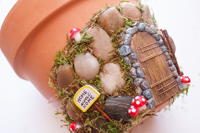 home sweet home, written on a small sign, attached to a decorated ceramic pot, fairy garden ideas, pebbles and little mushroom decorations, tiny painted door