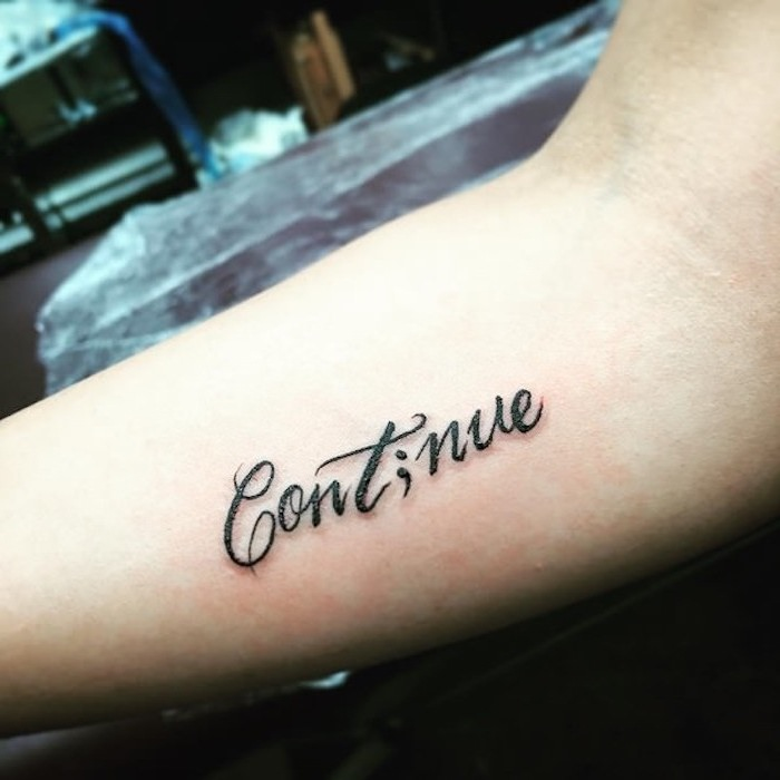 elegant black font, spelling the word continue,but with the i replaced with a semicolon, tattooed on the inside of a person's arm, semicolon tattoo meaning, spreading awareness for suicide prevention