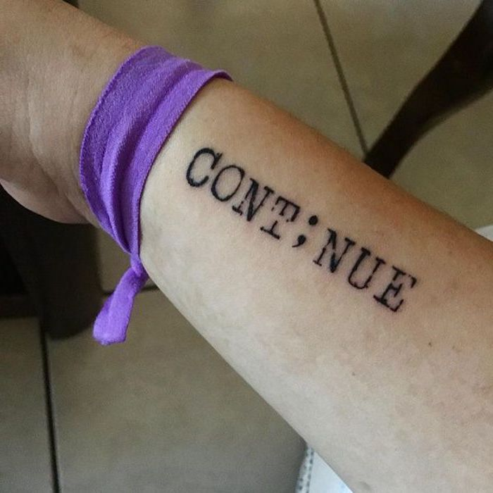 purple fabric wristband, tied to a person's hand, what does a semicolon tattoo mean, the word continue tattooed in a black, typewriter style font, the i replaced by a semicolon