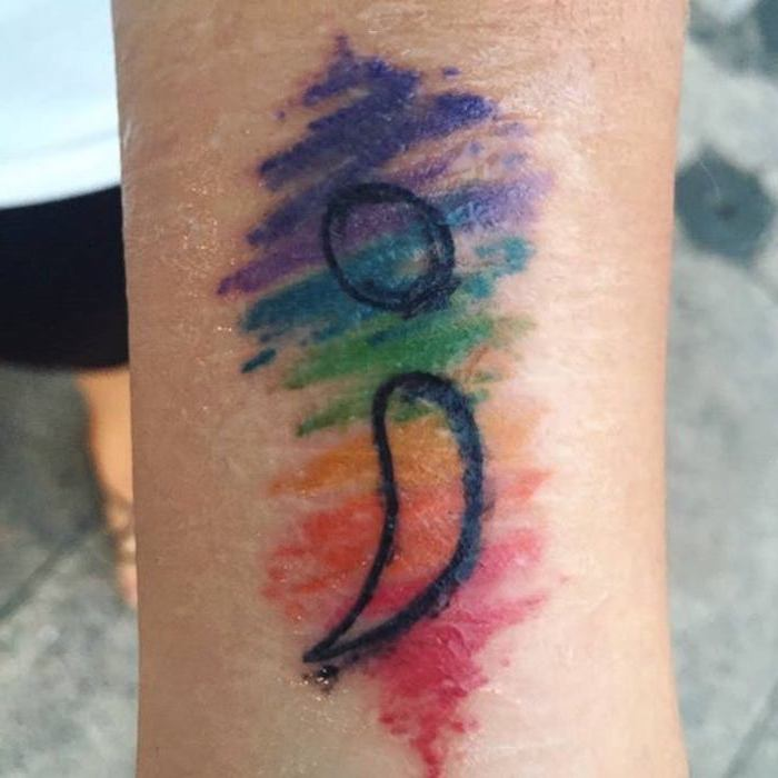 rainbow crayon scribble effect tattoo, with black semicolon outline, semicolon tattoo meaning, on a slim person's wrist