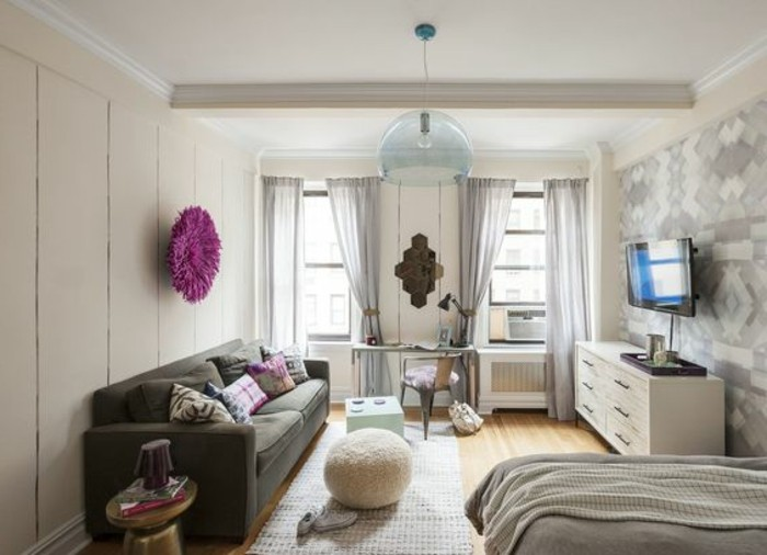 mink-colored sofa, with several cushions, small apartment living room ideas, purple wall ornament, pale gray curtains and wallpaper, bed with light gray covers