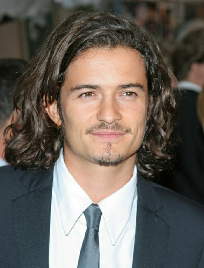 orlando bloom smiling, with medium length, brunette curly hair, combed over to one side, curly hairstyles, short mustache and goatee, formal suit with white shirt, and black shiny tie