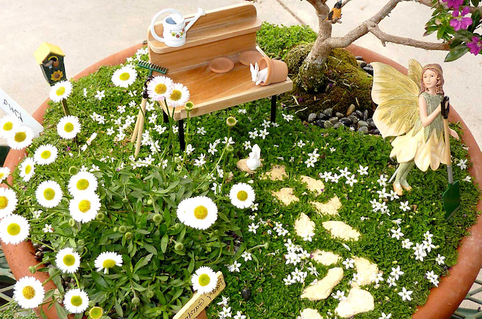 bench-shaped miniature wooden figurine, inside a large ceramic pot, with daisies and tiny white flowers, fairy garden images, decorated with a yellow and green fairy figurine, holding a shovel