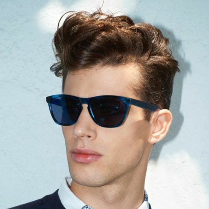 hairstyles for short curly hair, youth with dark blue sunglasses, wearing a pompadour, made from his brunette curly hair