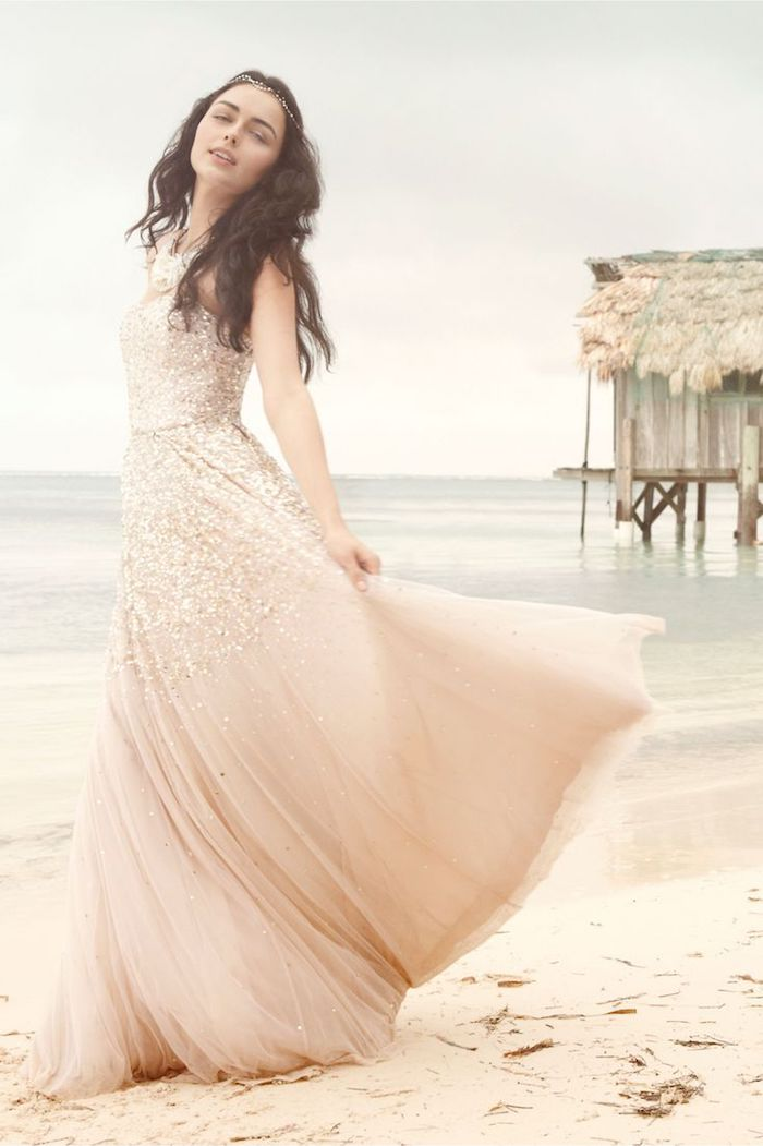 pale pastel pink wedding dress, with rose gold sequins, and a flowy tulle skirt, worn by dark-haired girl, standing on a beach