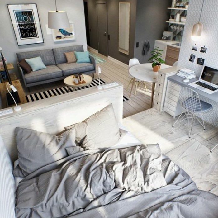 messy bed in white and gray, near blue-gray desk and matching chair, light wooden floor, grey sofa and white round table, small apartment ideas, framed artworks and shelves